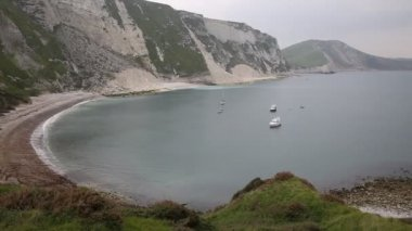 Boats in Mupe Bay shingle beach east of Lulworth Cove Dorset England and is part of the Jurassic Coast World Heritage Site — Stock Video