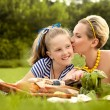 Happy mother and daughter kissing outdoors. Family picnic — Stok fotoğraf