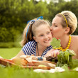 Happy mother and daughter kissing outdoors. Family picnic — Stock Photo