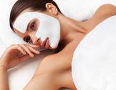 Young woman at spa salon with cosmetic mask on face. — Stock Photo