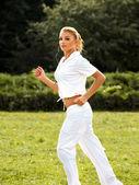 Atletico corridore di formazione in un parco per la maratona. ragazza fitness — Foto Stock