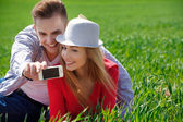 Couples with phone taking selfie self portrait at the park — Stok fotoğraf