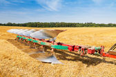 Plough ready to work on stubble field — Stock Photo