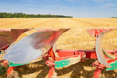 Detail of agriculture plow and stubble field — Stock Photo