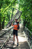 Hombre tiene una bicicleta gris en las manos y sonrisas — Foto de Stock