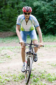 Young man bikes in the forest on bike — Foto Stock