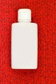 Weißen flasche auf roten teppich — Stockfoto