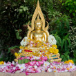 Stock Photo: Buddhstatue covered with flower petals after being cleansed an