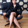 Confident woman sitting on a leather chair — Stock Photo