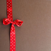Red ribbon on brown — Stock Photo