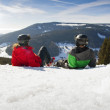 Young happy couple lying in snowy mountains. Winter sport vacation — Stock Photo