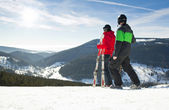 Young happy couple looking in snowy mountains holding ski. Winter sport vacation — Stock Photo