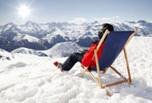 Women at mountains in winter lies on sun-lounger — Stock Photo