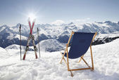 Cross ski und leere sonnenliege am berge im winter — Stockfoto