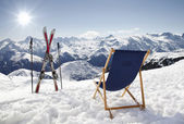 Cross ski and Empty sun-lounger at mountains in winter — Stock Photo