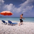 Sun lounger and umbrella on empty sandy beach — Stock Photo