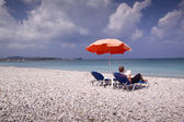 Sun longer and umbrella on empty sandy beach — Stock Photo
