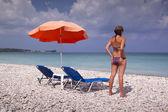 Sun lounger and umbrella on empty sandy beach — Stock Photo