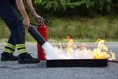Instructor showwing fire extinguisher — Stock Photo