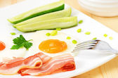 Breakfast with bacon, fried eggs and slices cucumber — Stock Photo
