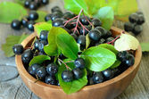 Black chokeberry in brown bowl — Stock Photo