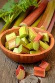 Fresh rhubarb on wooden garden table — Stock Photo