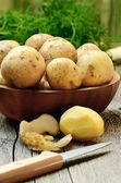 Raw potatoes on wooden table — Stock Photo