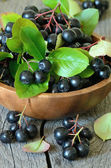 Black chokeberry on wooden table — Stock Photo
