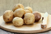 Raw potatoes in bowl on wooden table — Stock Photo