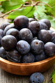 Plums in wooden bowl — Stock Photo