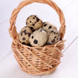 Quail eggs in wicker basket — Stock Photo