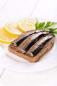 Sprats sandwich and lemon slices — Stock Photo
