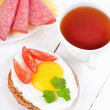 Sandwich with fried egg, tomato slices and tea — Stock Photo #47479325