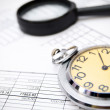 Stock Photo: Watch and magnifier on documents.