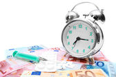 Tablets, a syringe and an alarm clock on money. — Stock Photo