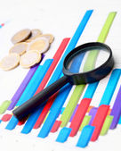Coins and a magnifier on Financial graphs. — Stock Photo