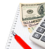 Red pen, the calculator and money on a notebook. — Foto de Stock