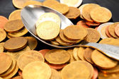 Spoon. A scattering of coins. — Stock Photo