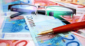Pen and Glasses on banknotes (euro). — Stock Photo