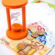 Sand-glass, coins and euro on graphs. — Stock Photo