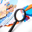 Magnifier, coins and banknotes on graphs. — Stock Photo