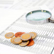Stock Photo: Coins and magnifier on documents.