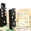 Dominoes on money (dollars). - Stock Photo