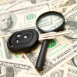 Keys from the car and a magnifier on money. — Stock Photo #18989917