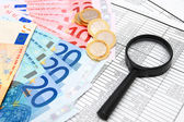 Magnifier, euro and coins on documents. — Stock Photo