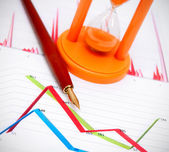 Pen and a sand-glass on graphs. — Stock Photo