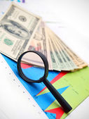 Magnifier and dollars on graphs. — Stock Photo
