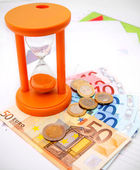 Sand-glass, coins and euro on graphs. — Stockfoto