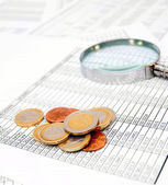 Coins and a magnifier on documents. — Stock Photo