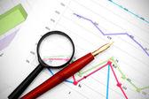 Lupa e caneta em gráficos financeiros. — Fotografia Stock